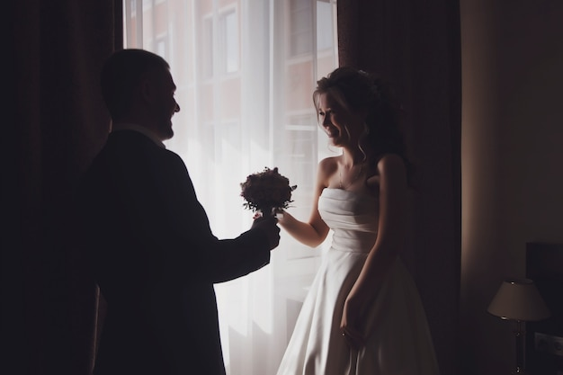 Happy groom gives cute bride bouquet of flowers at window in hotel room. morning of couple on wedding day. pretty young woman is wait to meet man. concept of happiness and luxury married. copy space