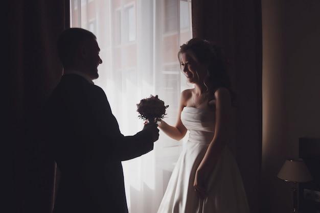 幸せな新郎はホテルの部屋の窓に花のかわいい花嫁の花束を与えます。結婚式の日のカップルの朝。かなり若い女性が男性に会うのを待っています。幸せと贅沢の概念が結婚しました。コピースペース