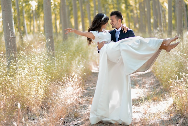 Happy groom holding bride in the countryside