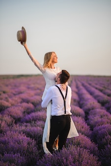 Happy groom holding his bride in his arms in blooming lavender field at sunset