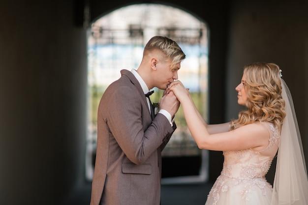 幸せな新郎は花嫁の手にキスします。休日やイベント
