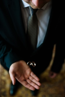 Happy groom with golden wedding rings on his hand. wedding day