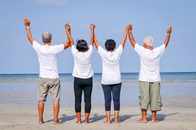 Happy group of elderly friends come to rest at the sea standing, holding hands and facing the sea
