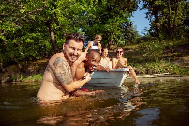 Felice gruppo di amici che si divertono mentre ridono e nuotano nel fiume. uomini e donne allegri in costume da bagno in una barca in riva al fiume nella giornata di sole. estate, amicizia, resort, concetto di fine settimana.