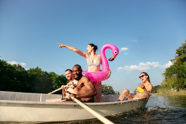 Happy group of friends having fun while laughting and swimming in river. joyful men and women in swimsuit in a boat at riverside in sunny day. summertime, friendship, resort, weekend concept.