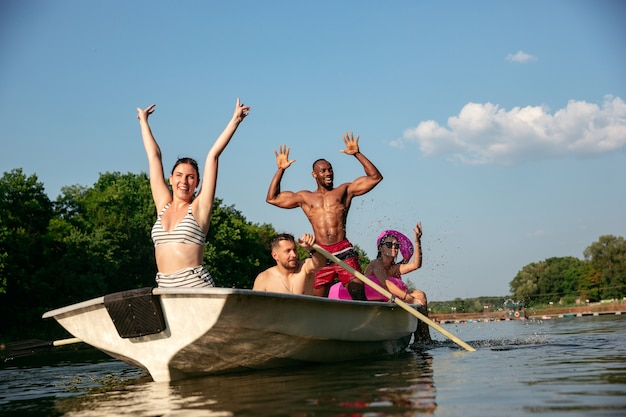 Happy group of friends having fun while laughting and swimming in river