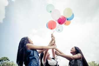 Happy group girl friends hand holding multicolored balloons