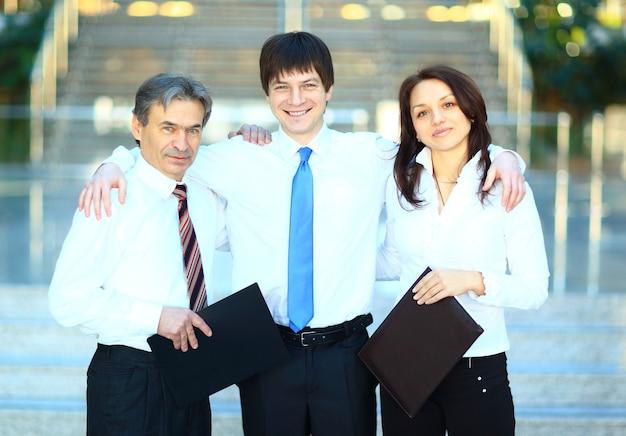 オフィスで笑っているビジネスマンの幸せなグループ