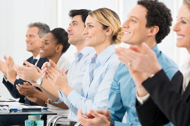 会議室で拍手するビジネスマンの幸せなグループ