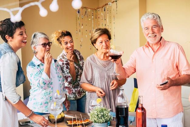 陽気な白人男性と女性の幸せなグループが、年齢を混合して楽しんで、一緒に食事をしたり、飲んだりして祝う