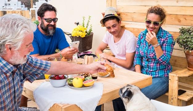 太陽の下のテラスで一緒に朝食を楽しんでいる家族の幸せなグループ。年配の男性が犬に小さなケーキをあげる