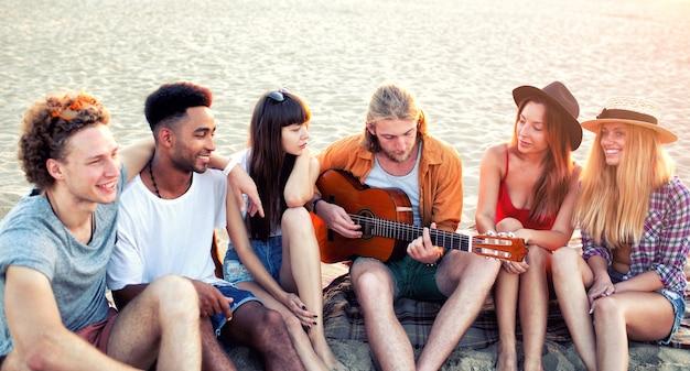 パーティーを開いてビーチでギターを弾く友人の幸せなグループ