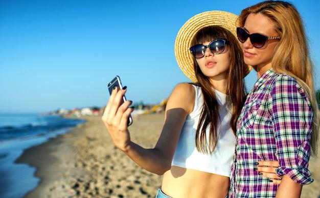 친구의 행복한 그룹이 소셜 네트워크를 위해 휴대 전화로 셀카를 만듭니다.