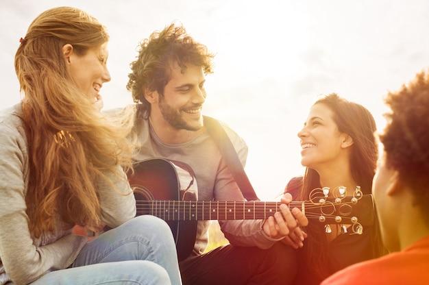 Счастливая группа друзей, наслаждающихся летом на открытом воздухе, играя на гитаре и поющих вместе