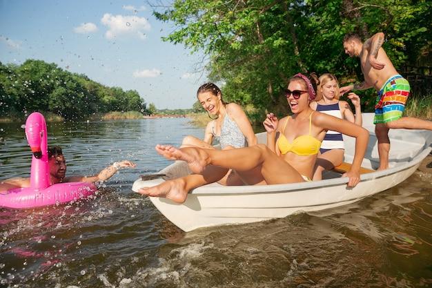 川で楽しんで、笑って、泳いでいる友達の幸せなグループ