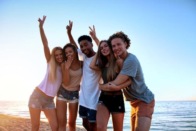 ビーチで楽しんでいる友達の幸せなグループ。夏のコンセプト