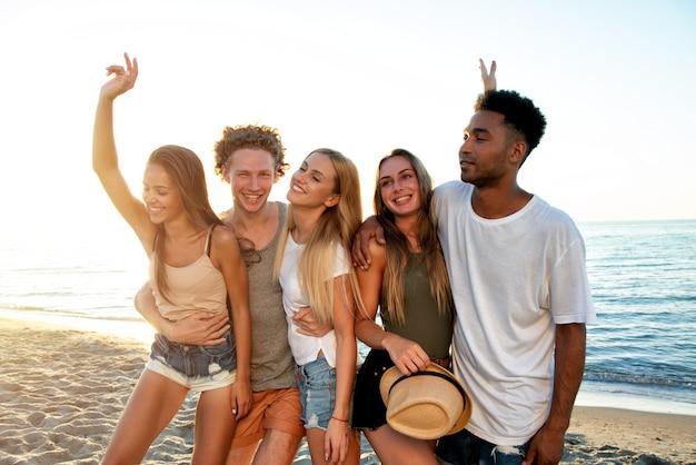 ビーチで楽しんでいる友達の幸せなグループ