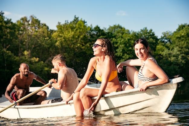Счастливая группа друзей весело смеясь и купаясь в реке.