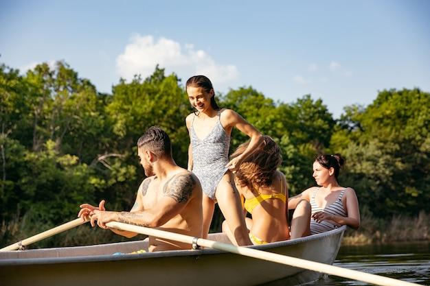 Счастливая группа друзей весело смеется и плавает в реке