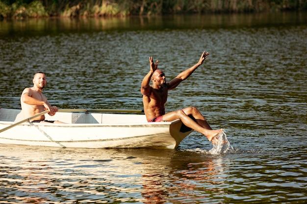 Счастливая группа друзей веселится, смеясь, плещется и плавает в реке