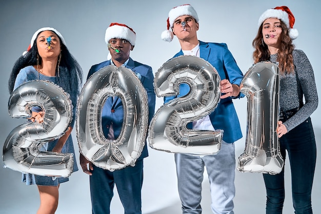 新年のお祝いの間に気球2021を保持している友人の幸せなグループ。休日のコンセプト