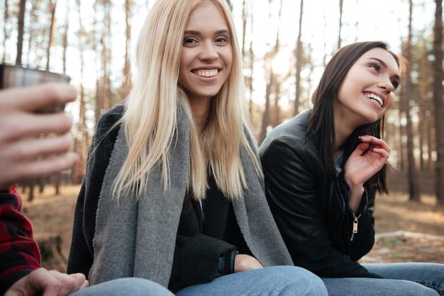 森の屋外で座っている友人の幸せなグループ。