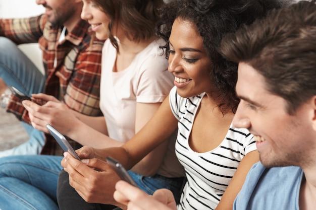 携帯電話のチャットを使用して友達の幸せなグループ。
