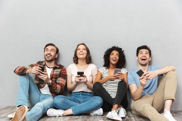 よそ見チャット携帯電話を使用して友達の幸せなグループ。