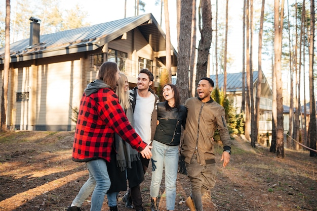 森で野外を歩いている友人の幸せなグループ。