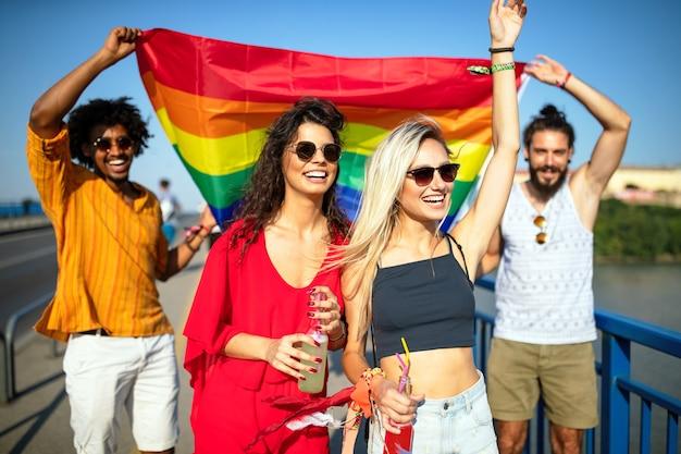 Счастливая группа людей, друзей, болтающихся в городе, размахивающих флагом гордости лгбт