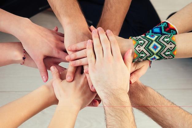 スタジオでヨガを練習している人々の幸せなグループ。ヨガのクラスでの瞑想とサポートのグループ。グループ瞑想とチームワークの概念。手のクローズアップ。支援グループ。