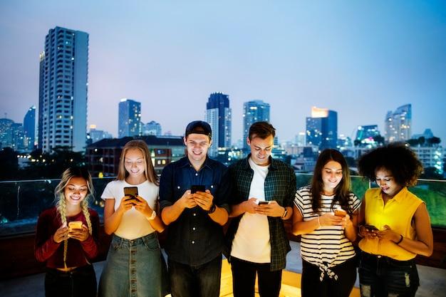 Счастливая группа молодых людей, использующих смартфоны в городском пейзаже
