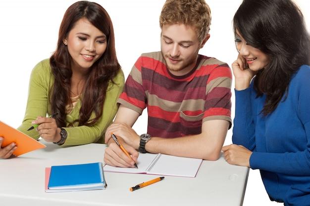 勉強している若い学生の幸せなグループ