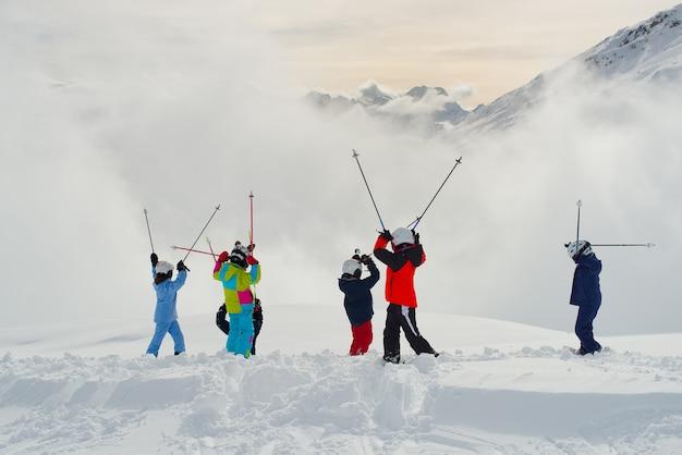 山でスキーを練習する幸せなグループ