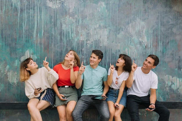 Happy group teenagers show something on the vintage background of copy space.