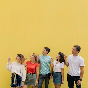 Happy group teenagers show something on the yellow background of copy space.