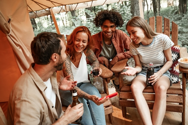 Happy group of young people drinking wine beer using phones social media during picnic in forest smiling millennial users customers talking shopping online sit at table, mobile tech lifestyle concept