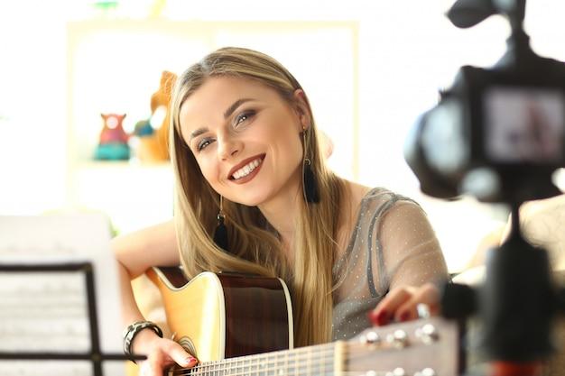 Happy guitar performer recording musical vlog
