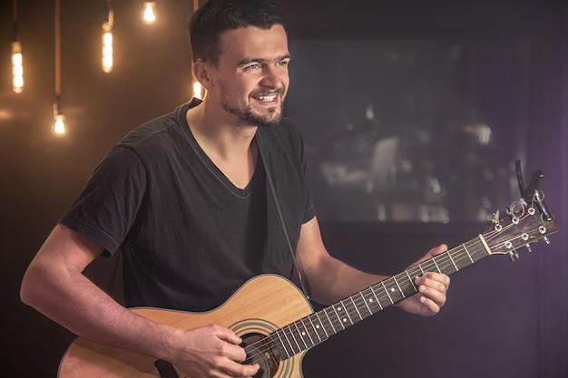 검은 티셔츠에 행복한 기타리스트가 콘서트에서 어쿠스틱 기타를 연주