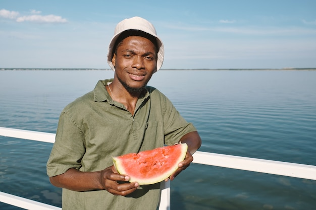 Happy guy of african ethnicity holding slice of juicy watermelon
