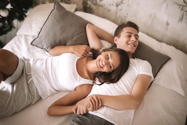 흰색 티셔츠를 입은 행복한 남자와 여자는 회색 베개가 있는 흰색 담요와 손을 잡고 침대에 누워 있습니다.