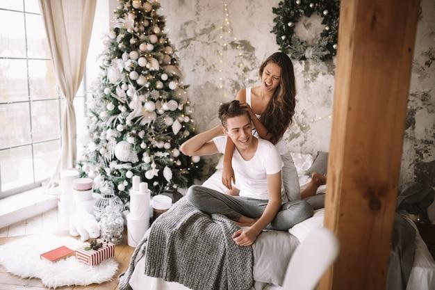 Счастливые парень и девушка в белых футболках сидят и обнимаются на кровати с серым одеялом в уютной оформленной комнате с новогодней елкой, подарками и свечами.