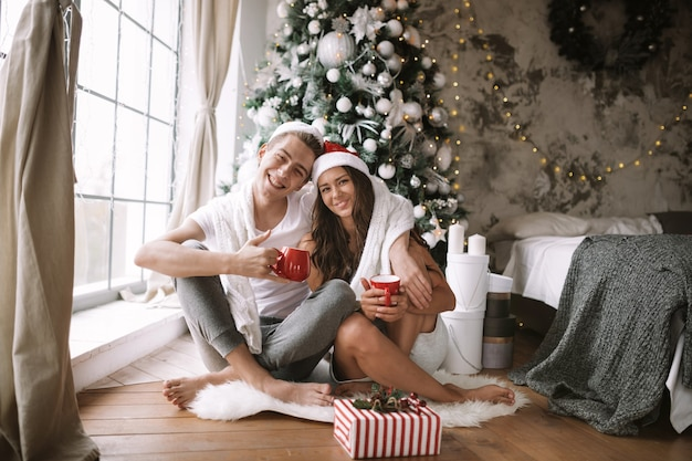 흰색 티셔츠와 산타클로스 모자를 쓴 행복한 남자와 여자는 새해 나무, 선물, 촛불 옆 창문 앞 바닥에 빨간 컵과 함께 앉아 있습니다.