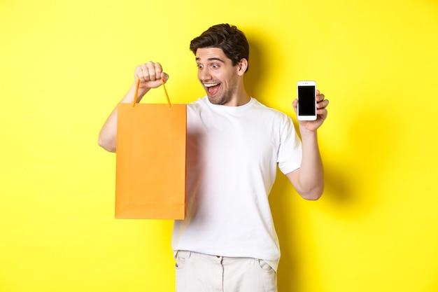 행복한 사람이 상점에서 물건을 구입하고 쇼핑백을보고 휴대 전화 화면, 노란색 벽을 표시합니다.