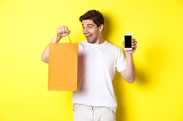 Happy guy buy something in store and looking at shopping bag, showing mobile phone screen, yellow wall