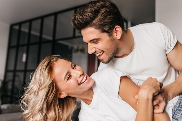 ガールフレンドと踊る幸せな男。家で楽しんでいる若者の笑顔。