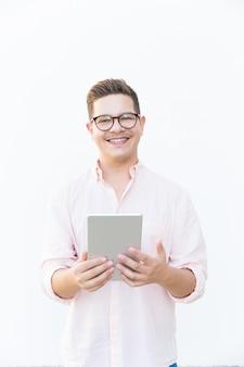 Happy guy in eyeglasses holding tablet