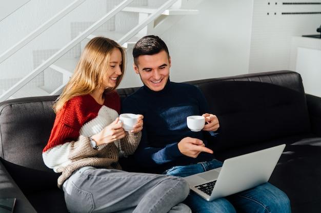 Felice ragazzo e ragazza guardando lo schermo del laptop, guardando un film, divertirsi insieme