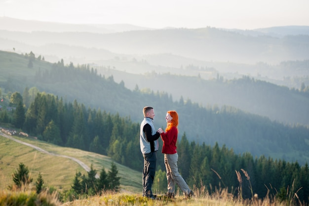 Happy guy and girl standing facing each other on a hill at the mountains in the morning