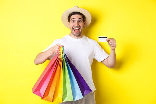 Happy guy going shopping on vacation, holding paper bags and showing credit card, standing over yellow wall